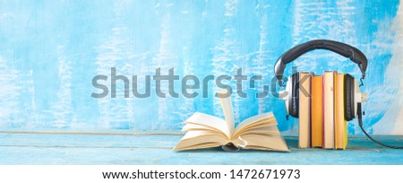 audio book concept with open book, row of books an headphones, panorama format on grungy background, good copy space