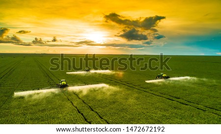 Agricultural sprayers making application at the end of the day with beautiful sunset #1472672192