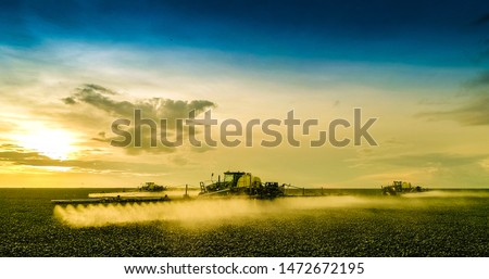 Agricultural sprayers making application at the end of the day with beautiful sunset #1472672195