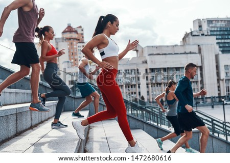 Group of young people in sports clothing jogging while exercising on the stairs outdoors                     #1472680616