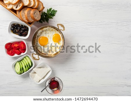 Daily Turkish breakfast concept ( Bread, black tea, tomatoes, cucumbers, olives, cheese and scrambled eggs ) #1472694470