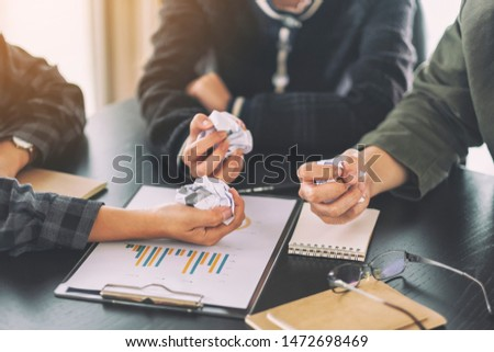 A businessman screwed up papers by hands with laptop, tablet and paper work on the table in a meeting #1472698469