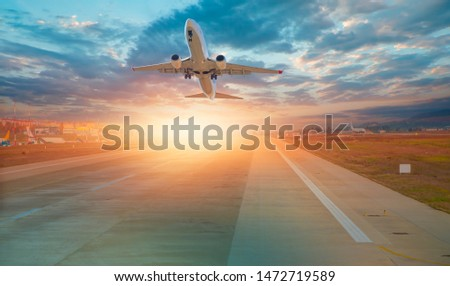 Airplane taking off from the airport at sunset - Travel by air transport #1472719589