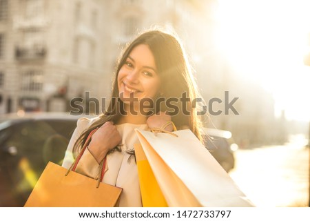 Cheerful woman doing shopping in a big city #1472733797