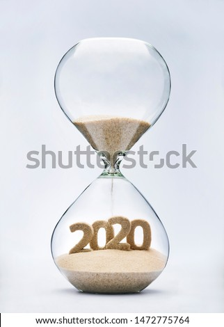 New Year 2020 concept with hourglass falling sand taking the shape of a 2020 #1472775764