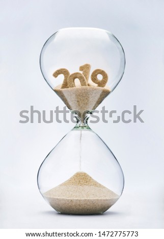 New Year 2020 concept. Time running out concept with hourglass falling sand from 2019. #1472775773