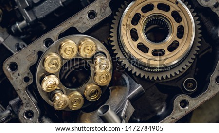 A service technician repairs a damaged hydraulic pump. Professional power hydraulics workshop. Hydraulic motor folding. Royalty-Free Stock Photo #1472784905