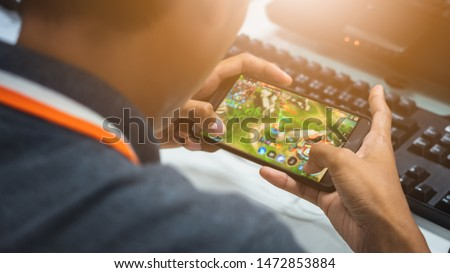 young boy who is playing online games in his mobile phone