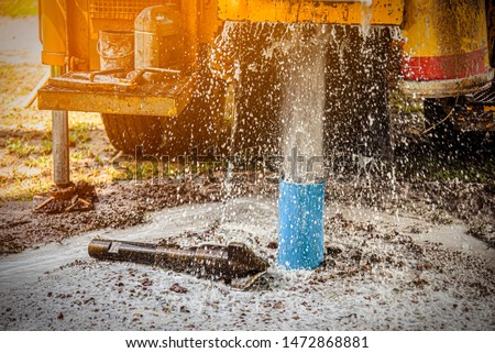 The water flowing artesian well from the land when the ground water hole drilling machine installed for the water supply. #1472868881