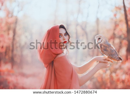 mystical pagan woman covered head peach scarf hood silk cape in autumn magic forest, holds barn owl bird. Portrait pretty face red lips. fantasy costume clothes. fog mist blossom tree spring garden #1472880674
