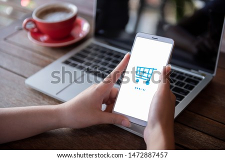 Young woman's hands are pressing the phone. Buy online   Women use computers smartphones and laptops to shop online