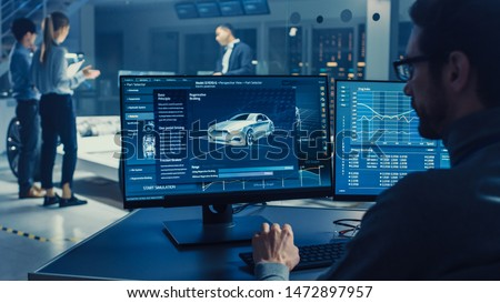 Professional Engineer Works on a Computer with a 3D CAD Software and Tests the Electric Car Chassis Prototype with Wheels, Batteries and Engine Standing in a High Tech Development Laboratory. #1472897957