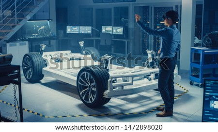 Automotive Engineer Working on Electric Car Chassis Platform, Using Augmented Reality Headset. In Innovation Laboratory Facility Concept Vehicle Frame Includes Wheels, Suspension, Engine and Battery. #1472898020