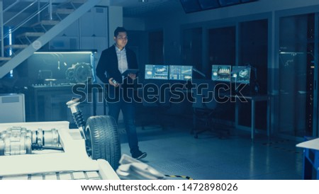 Development Laboratory Room with Professional Automotive Design Engineer Working on a Electric Car Chassis with Wheels, Batteries, Engine and Suspension. #1472898026