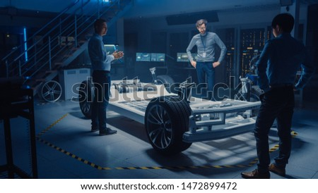 Diverse Team of Automobile Design Engineers Working Automotive Innovation Facility on Electric Car Platform Chassis Prototype that Includes Wheels, Suspension, Hybrid Engine and Battery #1472899472