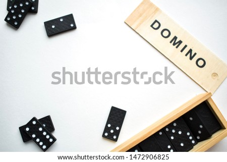 Game of dominoes, black dominoes on a white background with a wooden box of dominoes #1472906825