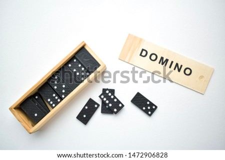Game of dominoes, black dominoes on a white background with a wooden box of dominoes #1472906828