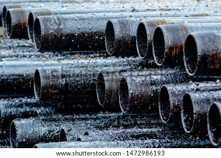 Oil Drill pipe. Rusty drill pipes were drilled in the well section. Downhole drilling rig. Laying the pipe on the deck. View of the shell of drill pipes laid in courtyard of the oil and gas warehouse. #1472986193