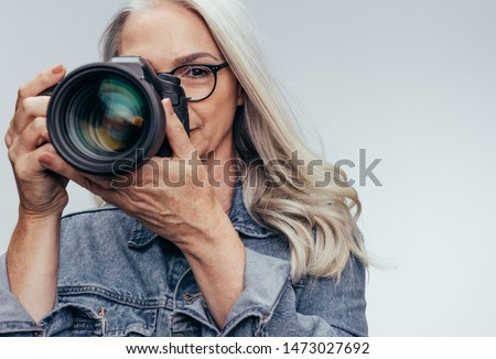 Mature female photographer taking pictures with dslr camera. Professional photographer doing a photoshoot.