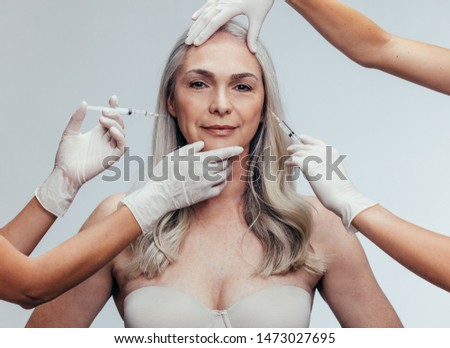 Senior woman gets injection in her lips and cheek by cosmetologists. Two beautician hands in gloves giving anti aging serum shot on female face against grey background #1473027695