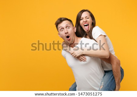 Shocked young couple two friends guy girl in white t-shirts posing isolated on yellow orange background. People lifestyle concept. Mock up copy space. Giving piggyback ride to joyful, sitting on back #1473051275