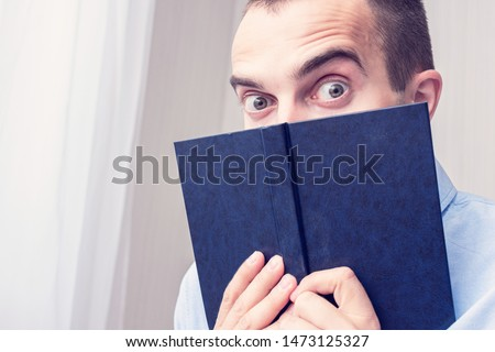 Shocked guy with the book, man reads the book, stares in surprise at the camera, raise his eyebrows, portrait, closeup, toned