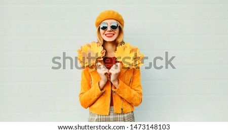 Autumn portrait happy smiling woman with yellow maple leaves on city street over gray wall background #1473148103