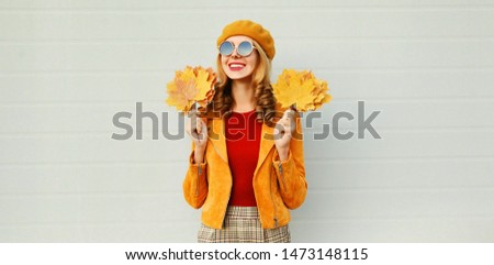 Autumn time! beautiful smiling woman with yellow maple leaves looking away on city street over gray wall background #1473148115
