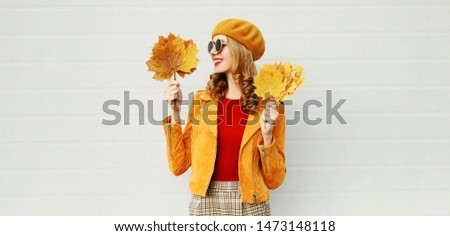 Autumn portrait smiling young woman looking on yellow maple leaves on city street over gray wall background #1473148118