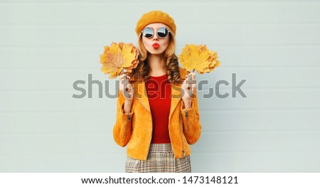 Autumn portrait woman holding yellow maple leaves blowing red lips sending sweet air kiss in french beret posing over gray wall background #1473148121