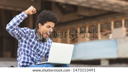 I did it. Young guy celebrating passing entrance exams checking list of students online on laptop, panorama with copy space #1473153491