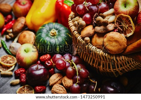 Autumn still life. Different fruits and vegetables in the wicker basket on the wooden table: pumpkin, grape, garlic, apple, nuts, peanuts, drain, bell peppers,  hot pepper and dry lemon slices  table  Royalty-Free Stock Photo #1473250991