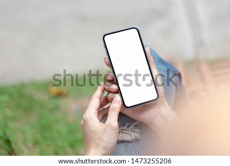 Mockup image screen cell phone.woman hand holding texting using mobile at outdoor.with white blank space for advertise text.concept for contact business,people communication,technology device #1473255206