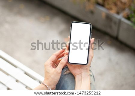 Mockup image screen cell phone.woman hand holding texting using mobile at outdoor.with white blank space for advertise text.concept for contact business,people communication,technology device #1473255212