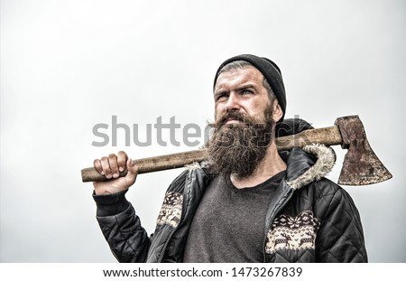 Hipster with beard on serious face carries axe on shoulder sky on background, copy space. Lumberjack brutal and bearded holds axe. Brutal lumberjack concept. Man in hat and warm jacket looks brutally. #1473267839