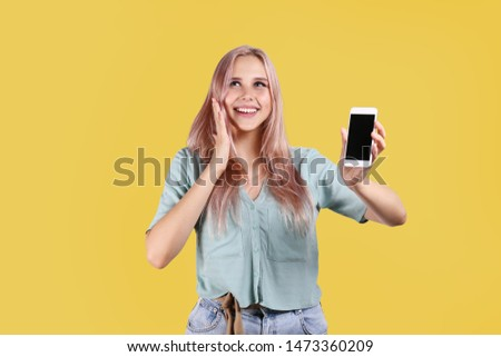 Young beautiful blonde woman with pink hair toner posing over bright colorful isolated background & holding smartphone. Portrait of teenage female model showing emotions. Close up, copy space. #1473360209