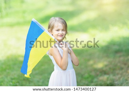 Child carries fluttering blue and yellow flag of Ukraine in field. Ukraine's Independence Day. Flag Day. Constitution day. Girl in traditional embroidery with flag of Ukraine #1473400127