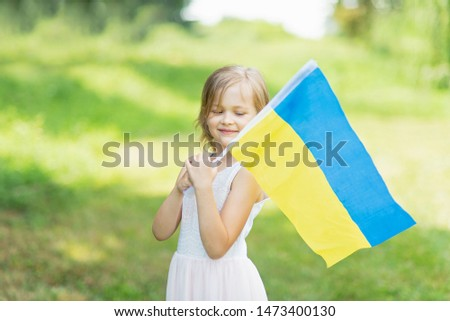 Child carries fluttering blue and yellow flag of Ukraine in field. Ukraine's Independence Day. Flag Day. Constitution day. Girl in traditional embroidery with flag of Ukraine #1473400130