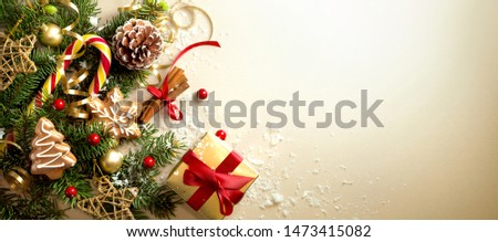 Christmas decoration composition on light gold background with beautiful Golden gift box with red ribbon, fir branches, cones, stars, Christmas cookies,cinnamon, top view, copy space, banner format. #1473415082