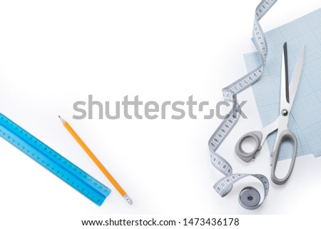 Creative flat lay composition of measuring tape, stainless steel sewing scissors, graph paper, ruler and pencil on a white background #1473436178