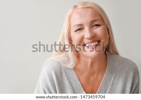 Happy mature woman on grey background #1473459704