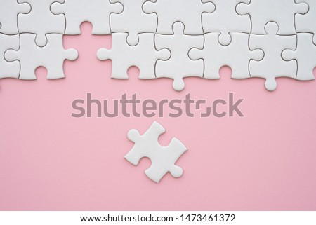 The last piece of jigsaw puzzle to complete task on pink background. Business strategy teamwork, problem solving concept. Teamwork is collaborative effort of team to achieve goal or complete mission.