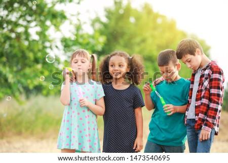 Cute little children blowing soap bubbles outdoors #1473540695