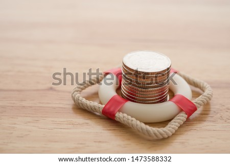 Stacked coins in red lifebuoy or lifebelt with wooden background copy space. Assets wealth, money saving or money investment protection and security by insurance concept. Risk management analysis. #1473588332