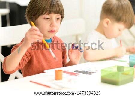 Cute kids doing their craft, painting at kindergarten #1473594329