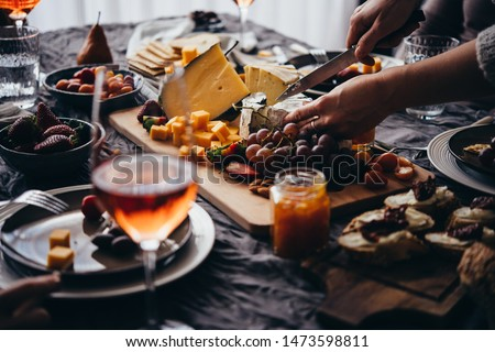 Friends having a dinner party with different kinds of appetizers and rose wine. #1473598811