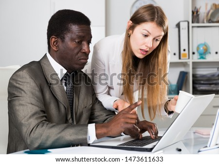 African businessman and Caucasian businesswoman sitting at desk and working at office #1473611633