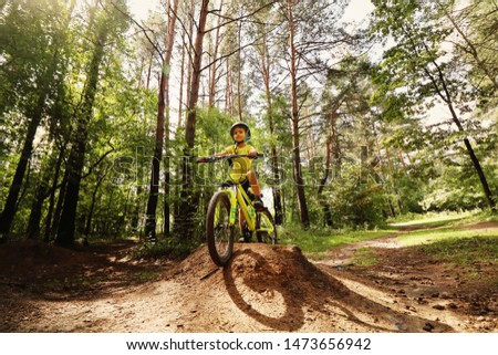 Young boy in the yellow t-short riding on the yellow bike in yhe wild forest.                       #1473656942