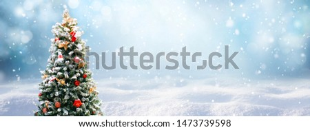 Beautiful Festive Christmas snowy background. Christmas tree decorated with red balls and knitted toys in forest in snowdrifts in snowfall outdoors, banner format, copy space. #1473739598