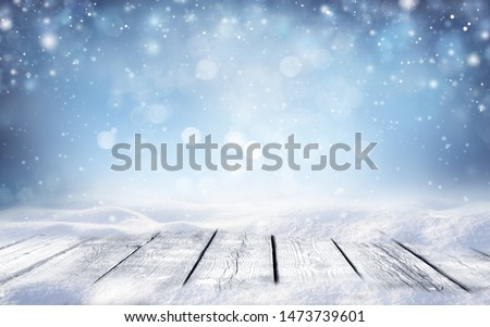 Beautiful winter snowy blurred defocused blue background and empty wooden flooring. Flakes of snow fall and sparkle on light, copy space. #1473739601